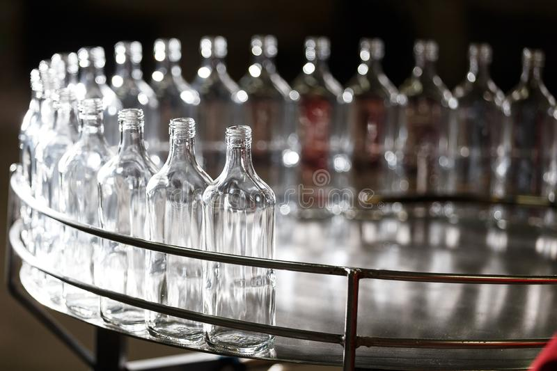 Empty glass bottles on the conveyor. Factory for bottling alcoholic beverages. Many bottles on conveyor belt in glass factory. Factory for bottling alcoholic royalty free stock photos