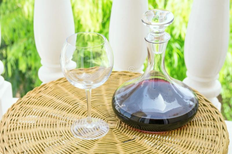 Empty Glass Decanter with Red Wine on Rattan Wicker Table in Garden Terrace of Villa or Mansion. Authentic Lifestyle Image. Relaxation Indulgence Gourmet stock image