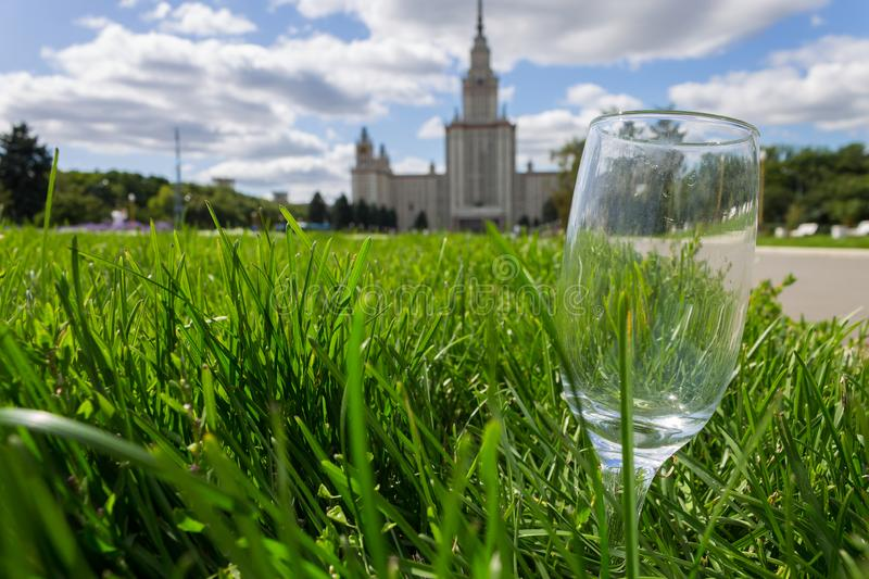 An empty glass lies in the thick green grass against the background of a large building stock photography