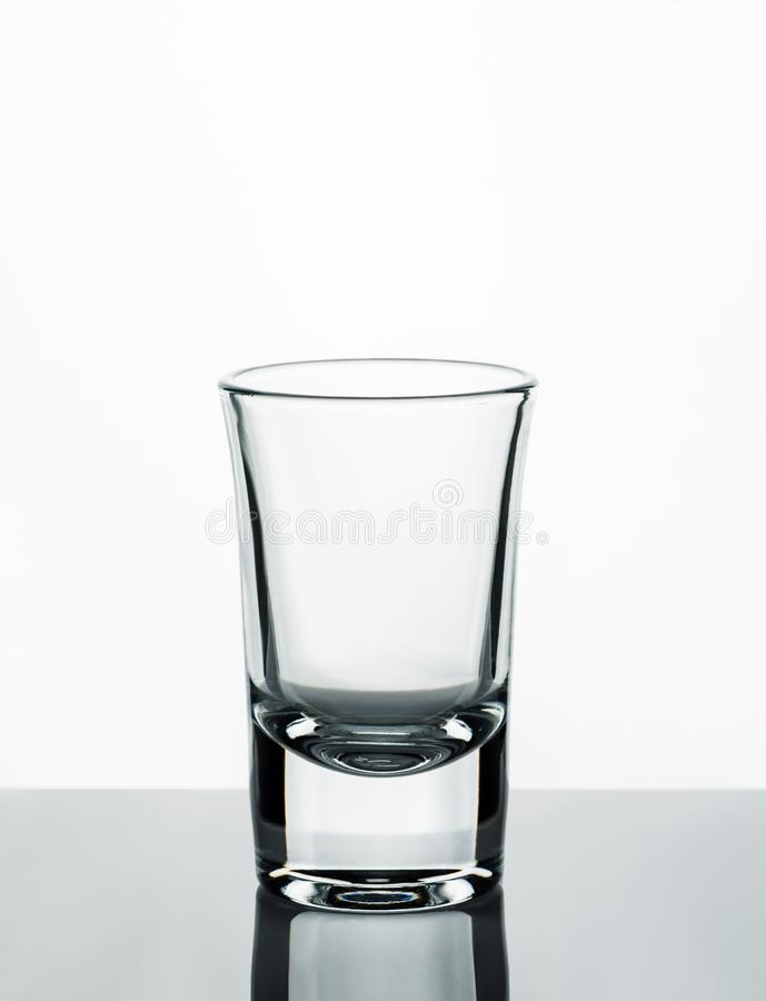 Empty glass shot on a reflective surface and white background.  royalty free stock photo