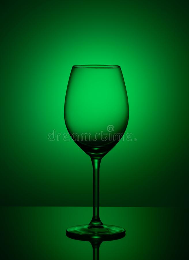 Empty glass stands on acrylic glass on a green background royalty free stock photography