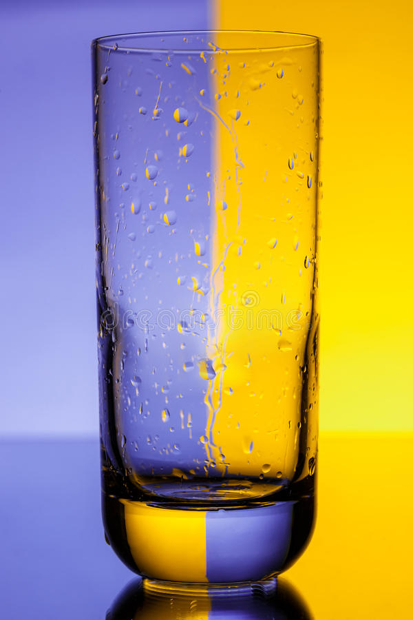 Empty glass with water drops over purple and yellow background. Copy space royalty free stock photography