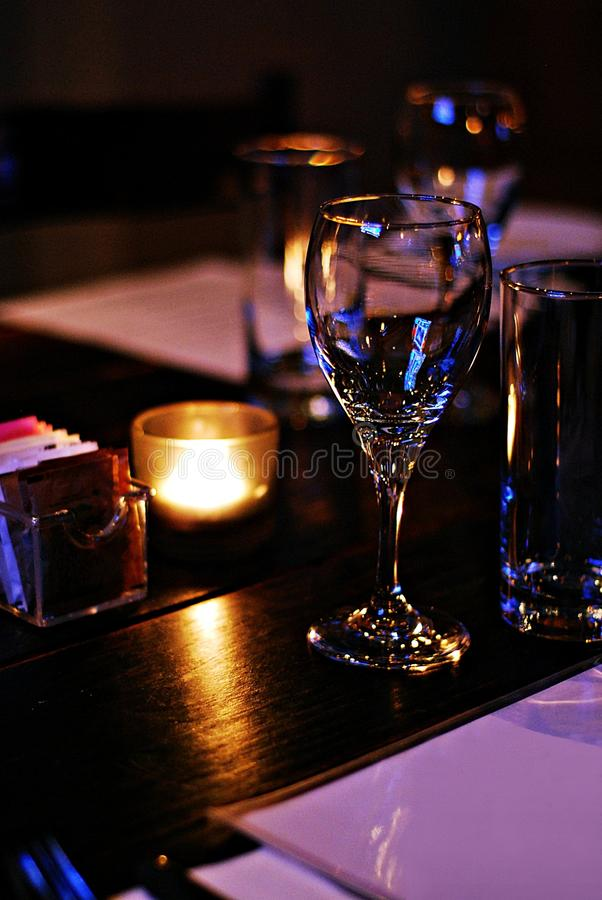 Empty glass of wine in chic restaurant dining room. Close up of an empty glass of wine in a chic restaurant dining room stock image