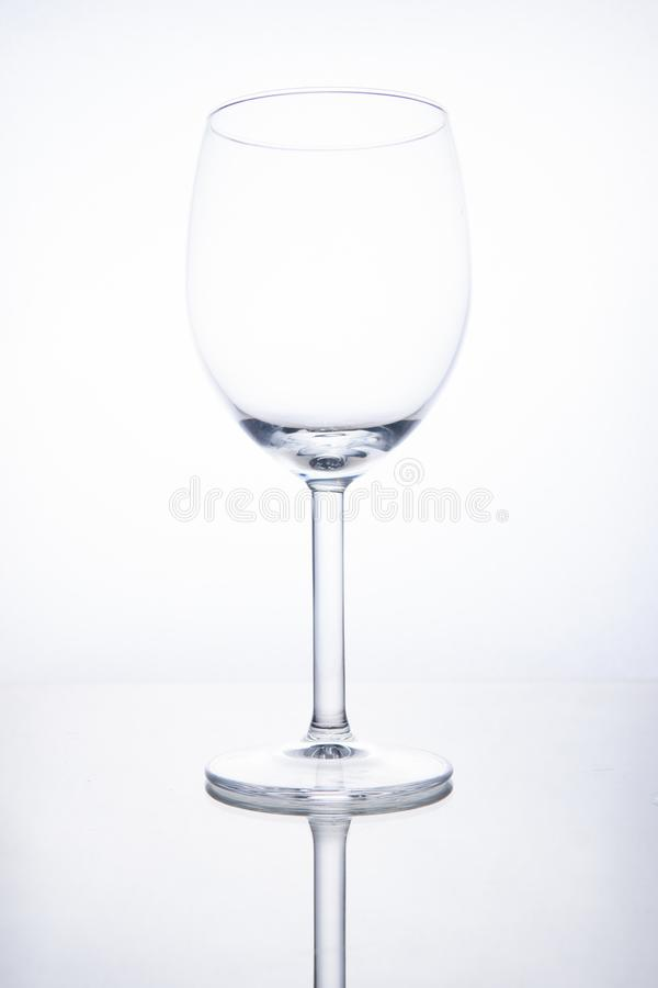 Empty glass wine goblet on white background with reflection stock images