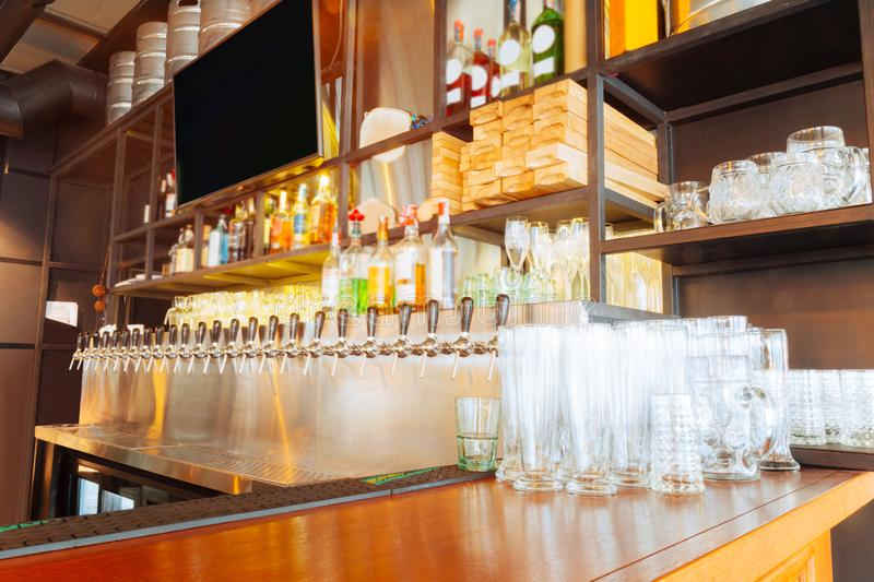 Big clean glasses standing empty of nice wooden bar stand. Empty glasses. Big clean glasses standing empty of nice wooden bar stand in modern restaurant royalty free stock images