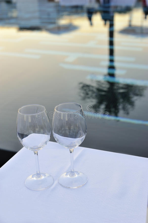 Empty glasses and pool on sunset royalty free stock image