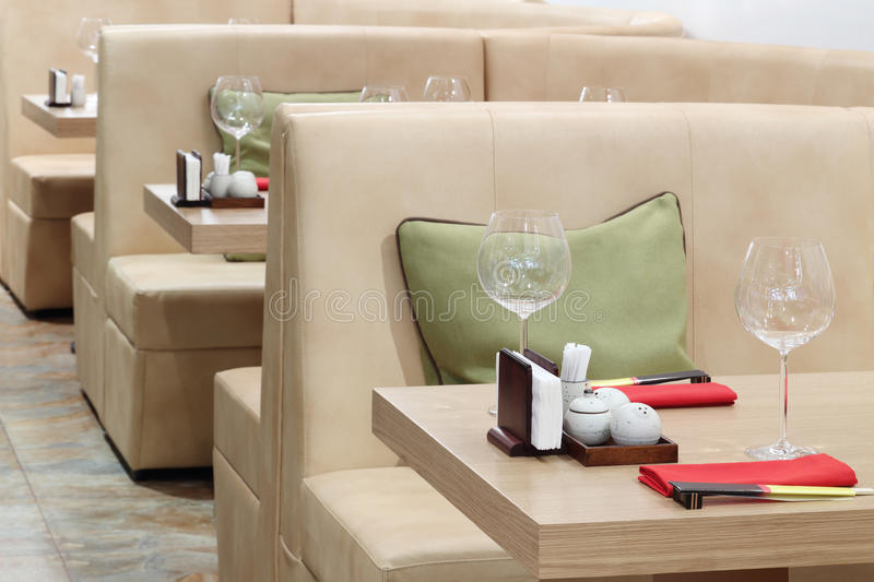 Empty glasses on tables and beige leather sofas. In Japanese restaurant stock photo