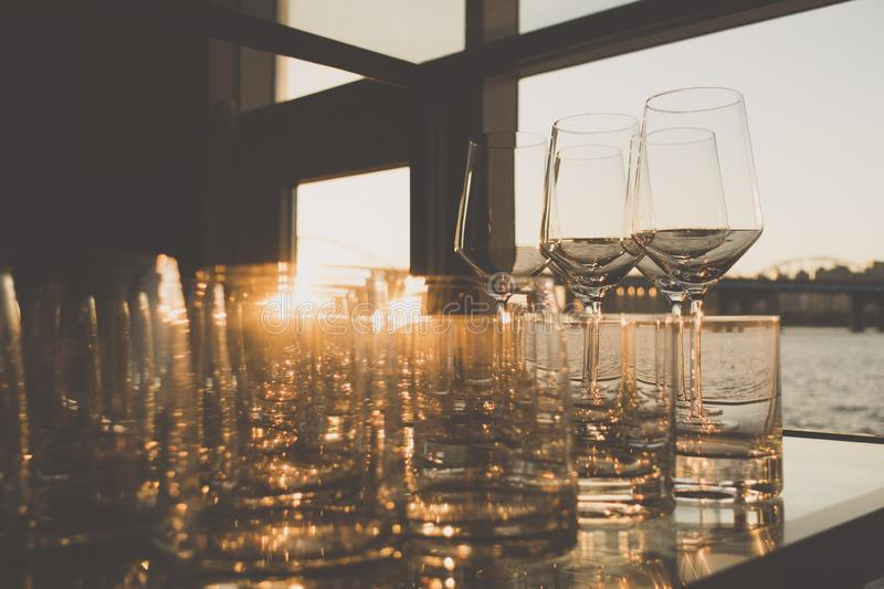 Empty glasses of whiskey and wine at sunset on indoor table with river view windows royalty free stock photos