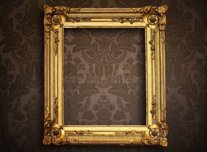 Empty golden frame on vintage wallpaper