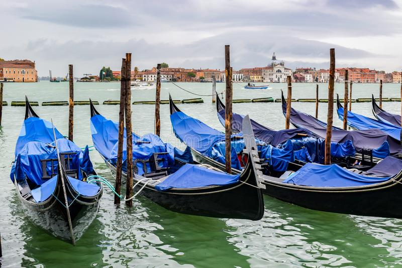 Empty gondolas docked between wooden mooring poles covered in tarpaulin in rainy November season in Venice, Italy stock images