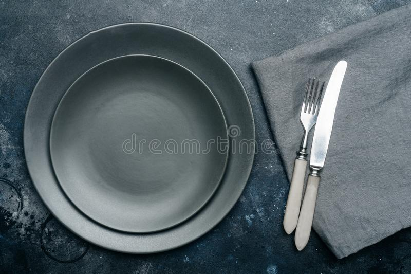 Empty gray plate ceramic on a dark gray background with a knife and fork, decorated with a bouquet of lavender and a napkin. royalty free stock photography