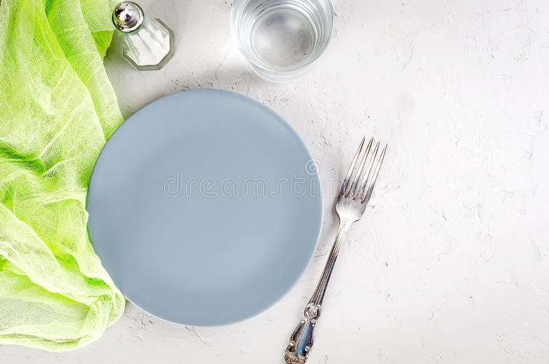 Empty gray plate serving for dinner. And cutlery on  gray concrete background. Top view, copy space stock images
