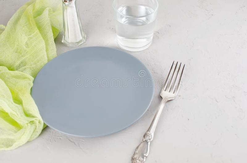 Empty gray plate serving for dinner. And cutlery on  gray concrete background. Top view, copy space royalty free stock photos