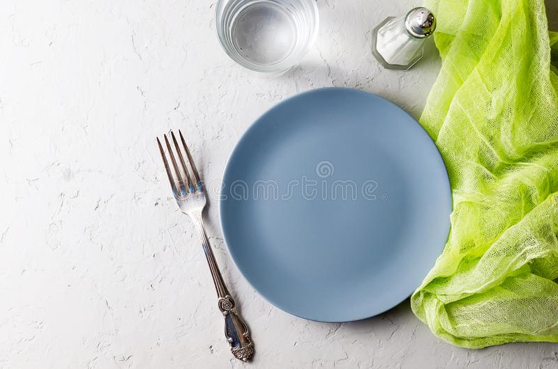 Empty gray plate serving for dinner. And cutlery on  gray concrete background. Top view, copy space stock photo