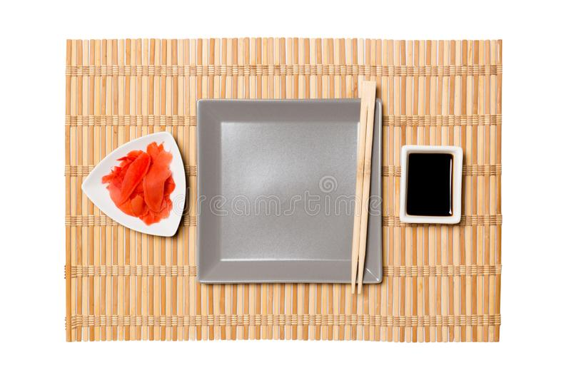 Empty gray square plate with chopsticks for sushi, ginger and soy sauce on yellow bamboo mat background. Top view with copy space royalty free stock image