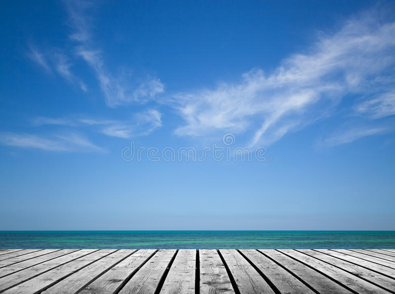 Empty gray wooden pier with sea and sky. Empty gray wooden pier with sea and cloudy sky on background stock image
