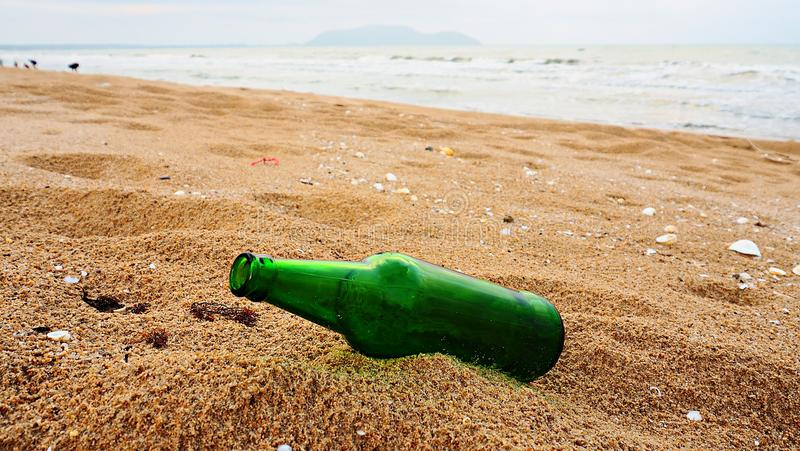 Empty green beer bottle on the beach. Concept of no garbage on beach stock photo