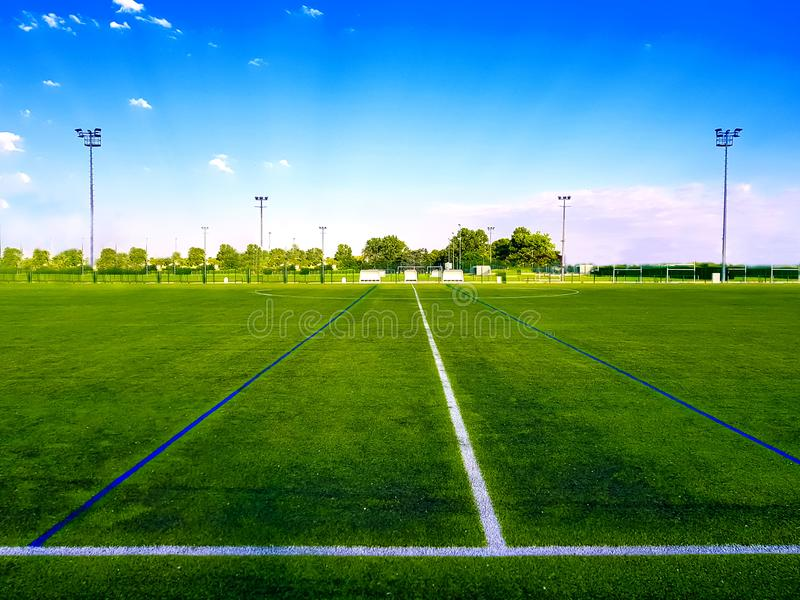 Empty green football field in the open air. Under blu sky stock image