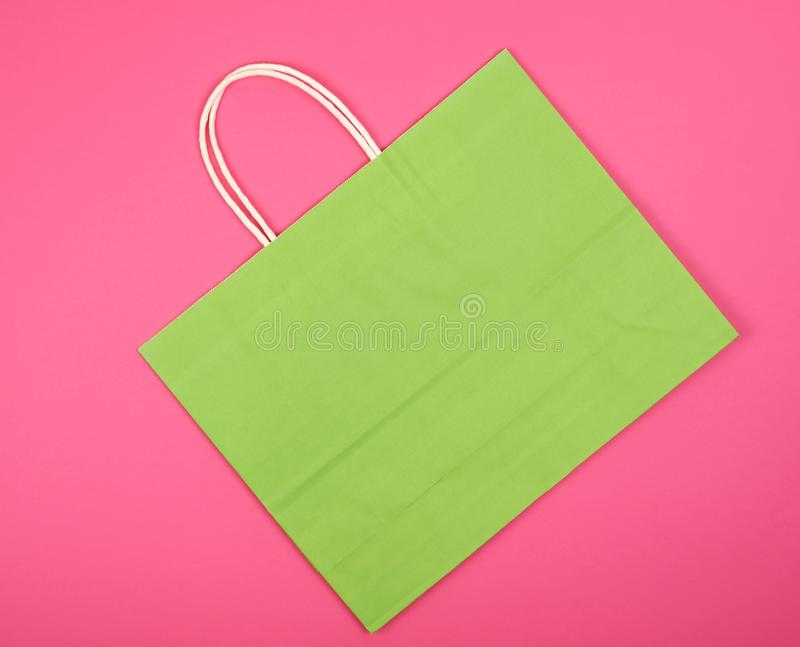 Empty green paper shopping bag with a handle. On a white background, close up royalty free stock photo
