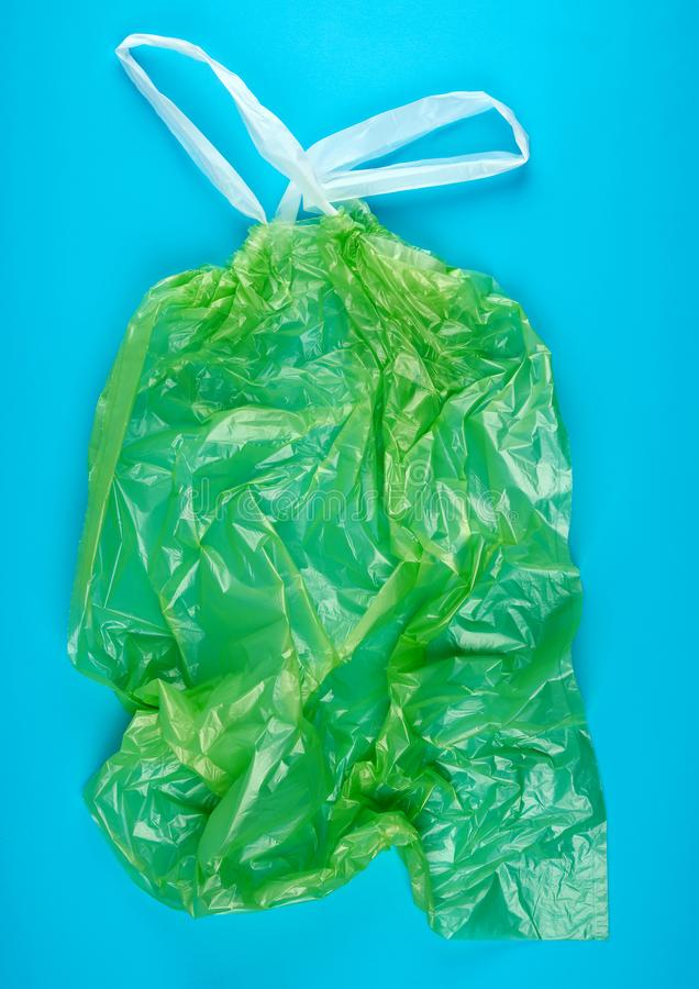 Empty green plastic garbage bag with handles. On a blue background stock images