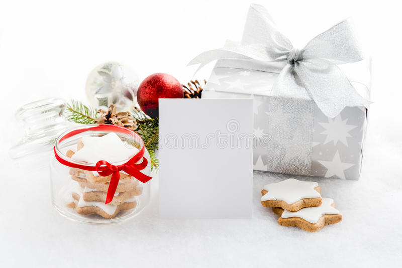 Empty greeting card and christmas gift box in silver wrapping paper over a white fluffy background. A jar full of star cookies. C. Hristmas decoration stock image