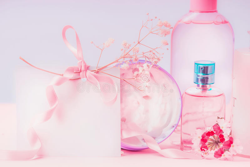 Empty greeting card laid and pink cosmetic products setting. Invitation, coupon, discount and sale. Beauty stock images