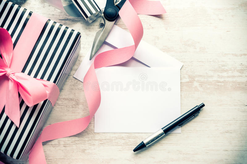 Empty greeting card. Wrapped gift and wrapping materials on a white wood background. Vintage style. royalty free stock images