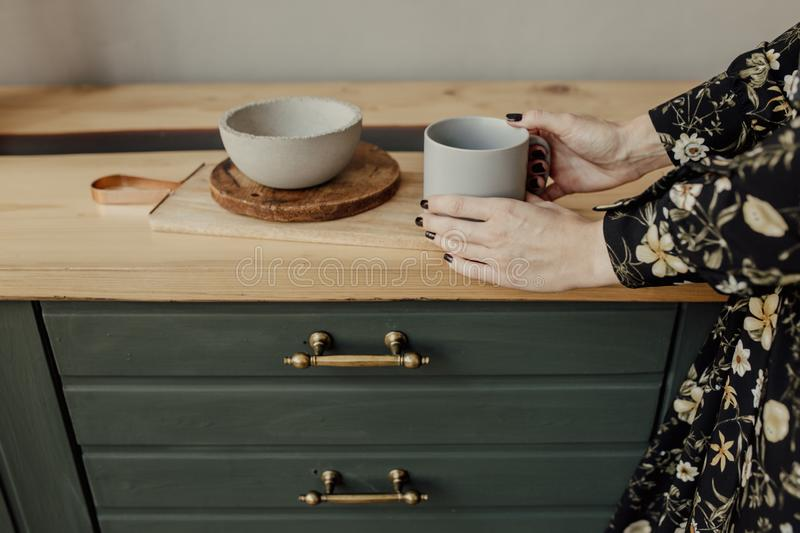 Empty grey cup and plate on old wooden are in girl` hands. Green kitchen stock photos