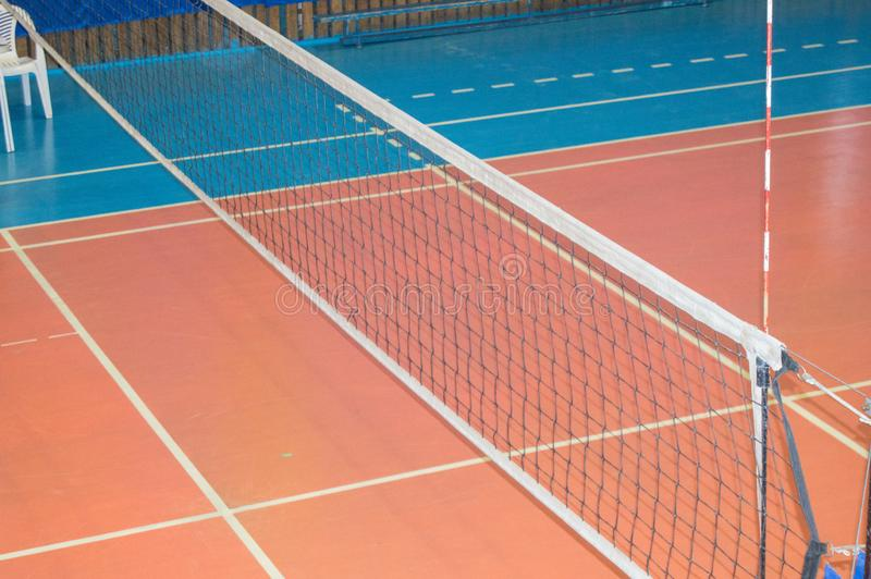 Empty gym with a stretched net for volleyball, against the background of orange and blue floor. Space for text. The concept of. Active sports, Hobbies, grid stock images