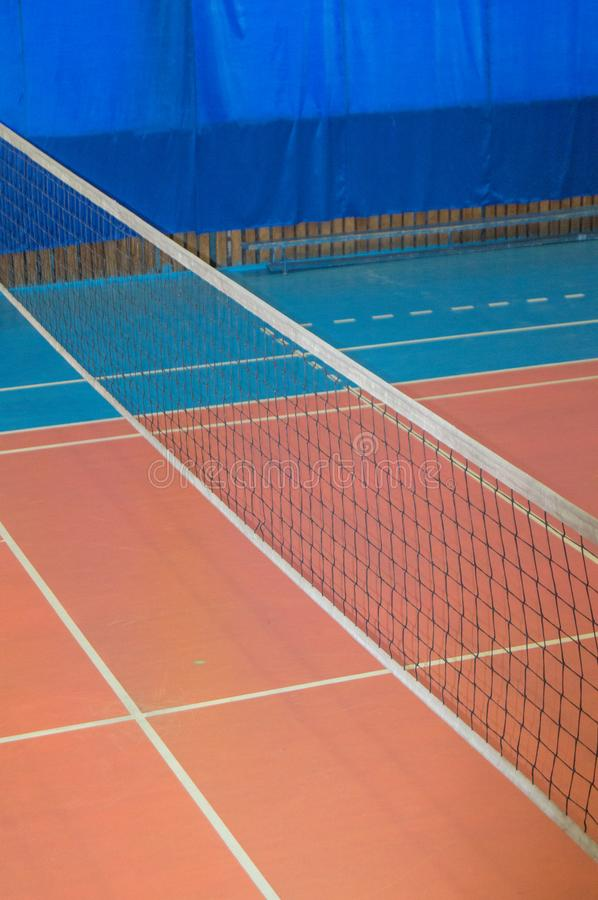 Empty gym with a stretched net for volleyball, against the background of orange and blue floor. Space for text. The concept of. Active sports, Hobbies stock photography