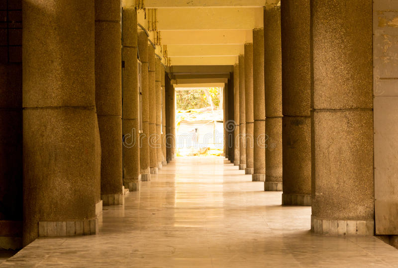 Empty hall with stone pillars and floor. Empty hallway in a school during the summer break. Stone pillars and shiny stone floor are visible stock image