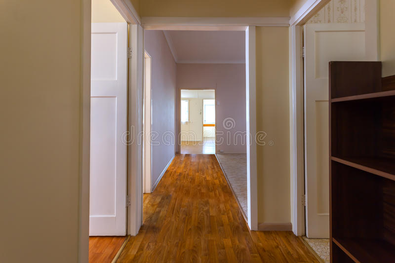 Empty hallway in a big house. Empty hallway with wooden floor in a big house connecting many rooms royalty free stock image