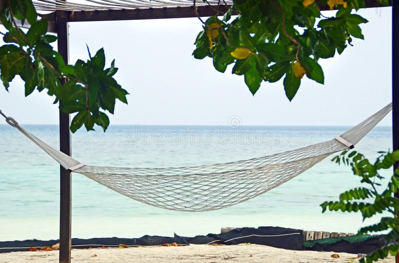 Beachfront hammock facing blue ocean on beach tropical island stock photography