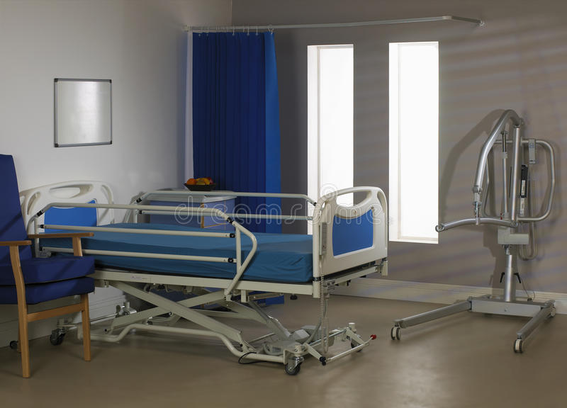 Empty hospital ward with bed chair and hoist. Empty hospital ward with bed hoist chair and curtain stock images