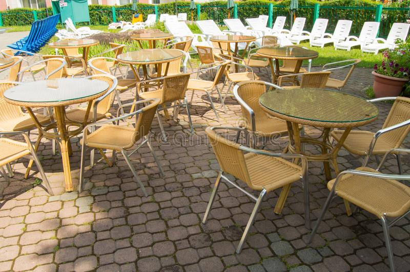 Empty hotel yard with swimming pool and patio. Wicker table and chairs, white plastic sun loungers on a Sunny summer day stock photo