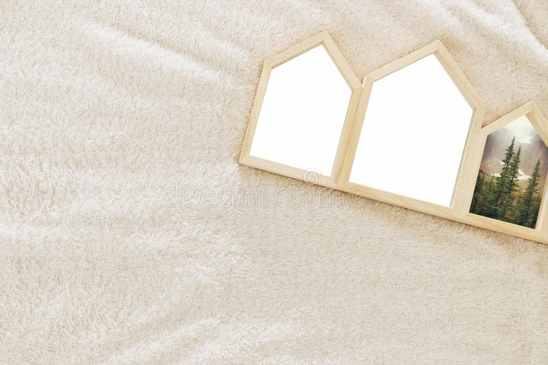 Empty houses shape wooden photo frames over cozy and warm fur carpet. For photography montage. Scandinavian style design. Top view royalty free stock photo
