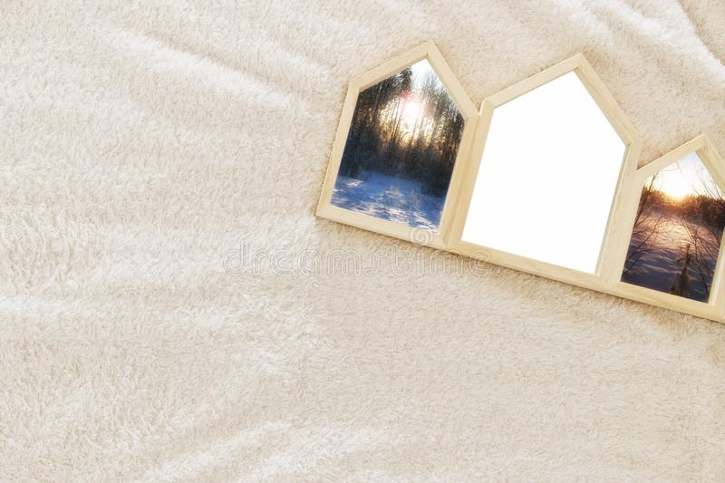 Empty houses shape wooden photo frames over cozy and warm fur carpet. For photography montage. Scandinavian style design. Top view royalty free stock photos