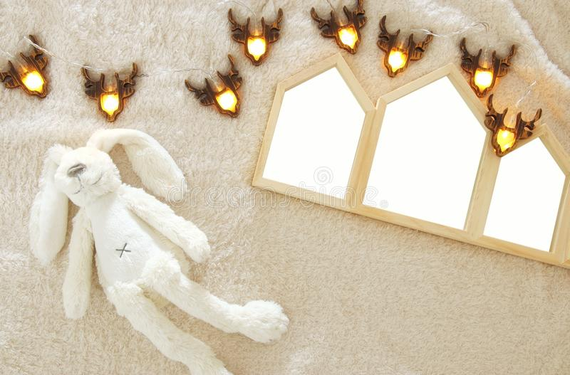 Empty houses shape wooden photo frames over cozy and warm fur carpet. For photography montage. Scandinavian style design. Top view stock image