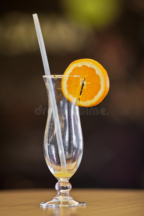 Empty hurricane glass with remains of orange juice stock photo