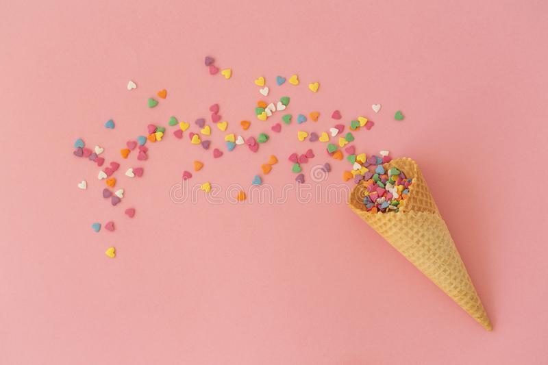 Empty ice-cream waffle cones and colorful sprinkles on pink background, top view. Scattering of multicolored sweets stock photography
