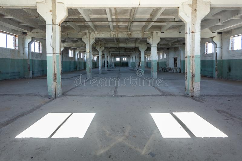 Industrial warehouse with cement walls, floors, windows and pillars before construction, remodeling, renovation. Empty industrial warehouse or commercial area in royalty free stock image