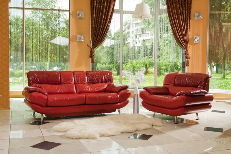 Empty light interior decorated with big red leather sofas and chairs. Nobody royalty free stock photo