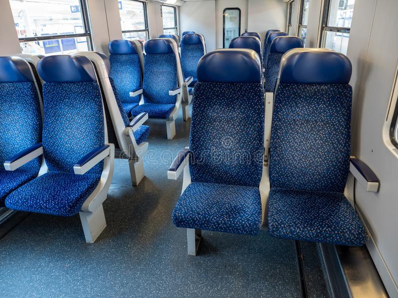 Empty Interior of a Railway Commuter Carriage. Empty Interior of a Railway Train Commuter Carriage with Blue Seats and White Walls stock photo