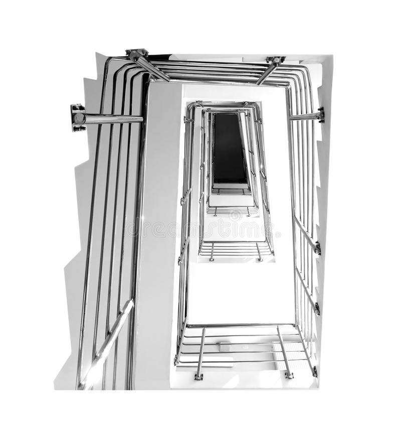 Empty internal staircase with a metal railing, going upward in a modern building with light walls. Black and white photo royalty free stock photo