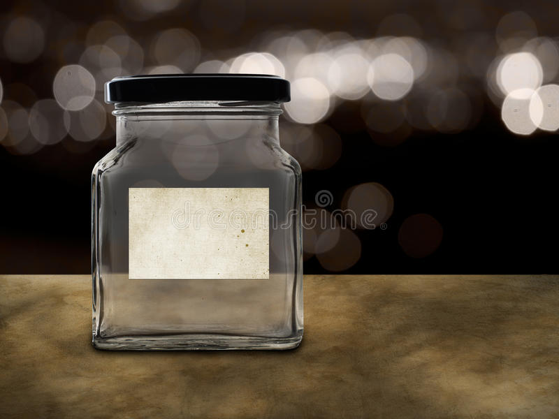 Empty jar with blank label. Savings, or school fees maybe. Many possible labels. Bokeh background as if at night stock image
