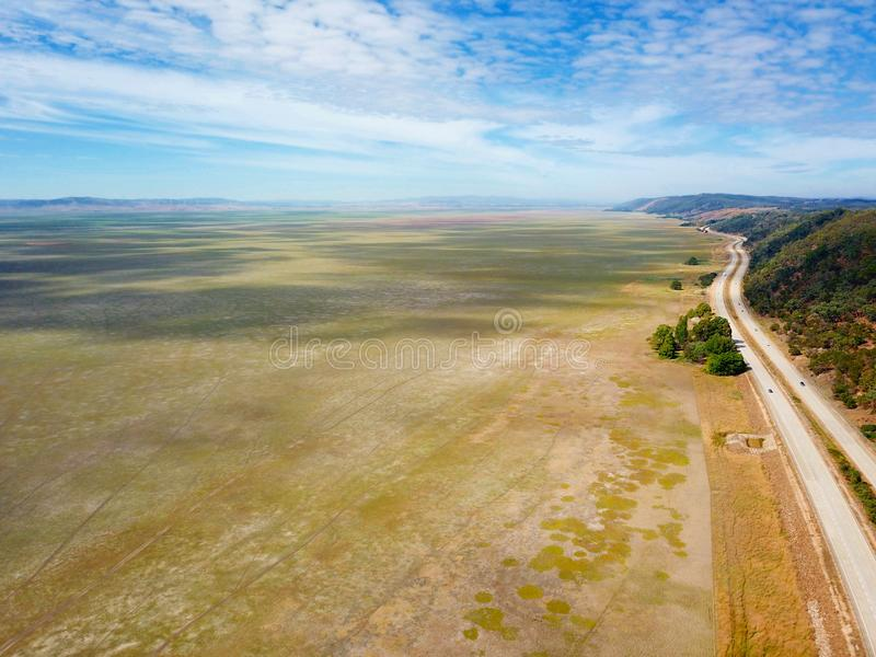Empty Lake George nestled between farmland and Federal Highway in Australia. Lake George is an endorheic lake, as it has no outflow of water to rivers and royalty free stock photos