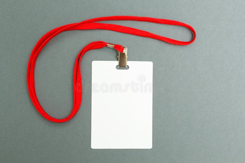 Empty layout layout isolated on black. A common blank label name tag hanging on the neck with a red thread on a gray background royalty free stock photo