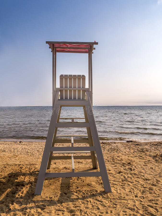 Empty lifeguard post. Empty wooden lifeguard post shot against the sea with clear blue sky stock image