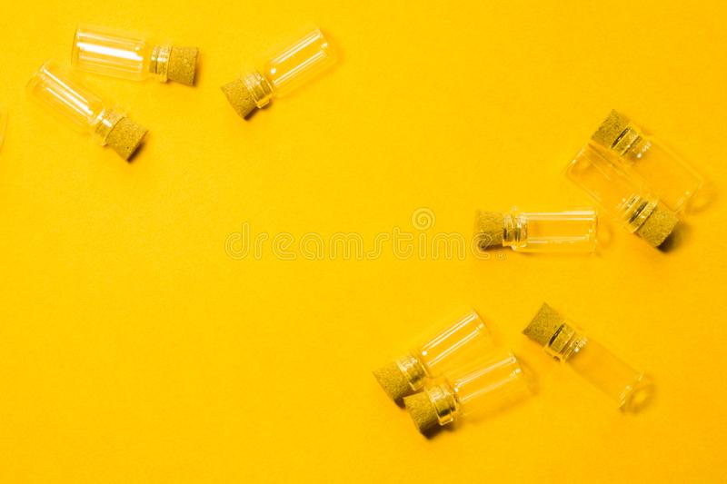 Empty little bottles with cork stopper isolated on yellow. transparent containers. test tubes. copy space. Empty little bottles with cork stopper isolated on royalty free stock photography