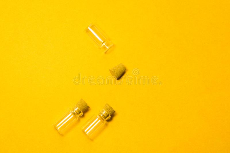 Empty little bottles with cork stopper isolated on yellow. transparent containers. test tubes. copy space. Empty little bottles with cork stopper isolated on stock images